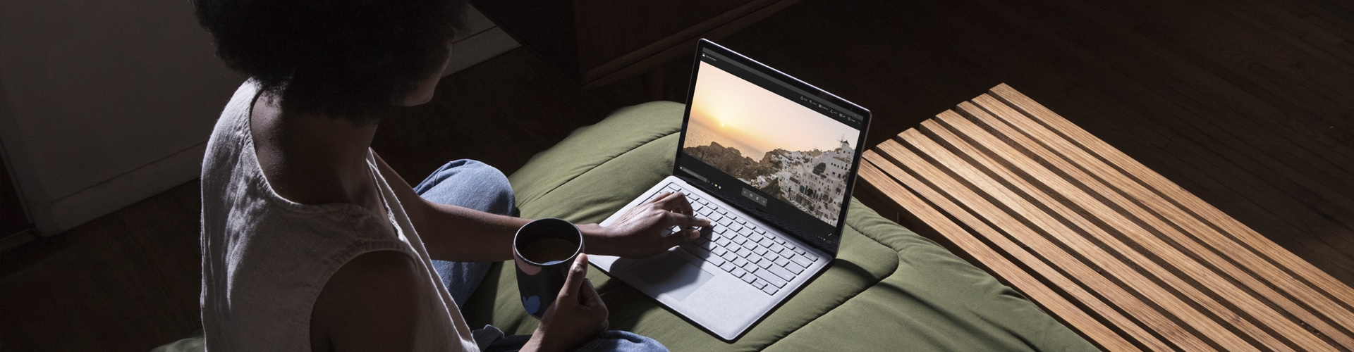 Photograph of person sitting cross-legged on a bed drinking something from a mug and using a laptop