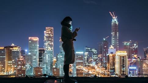 Kvinna på ett tak på natten som tittar på sin telefon