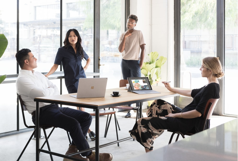 Four people seated around a small conference table having a meeting in a room bathed in natural light. One person is using a Surface laptop, and one person is using a Surface Pro in laptop mode.