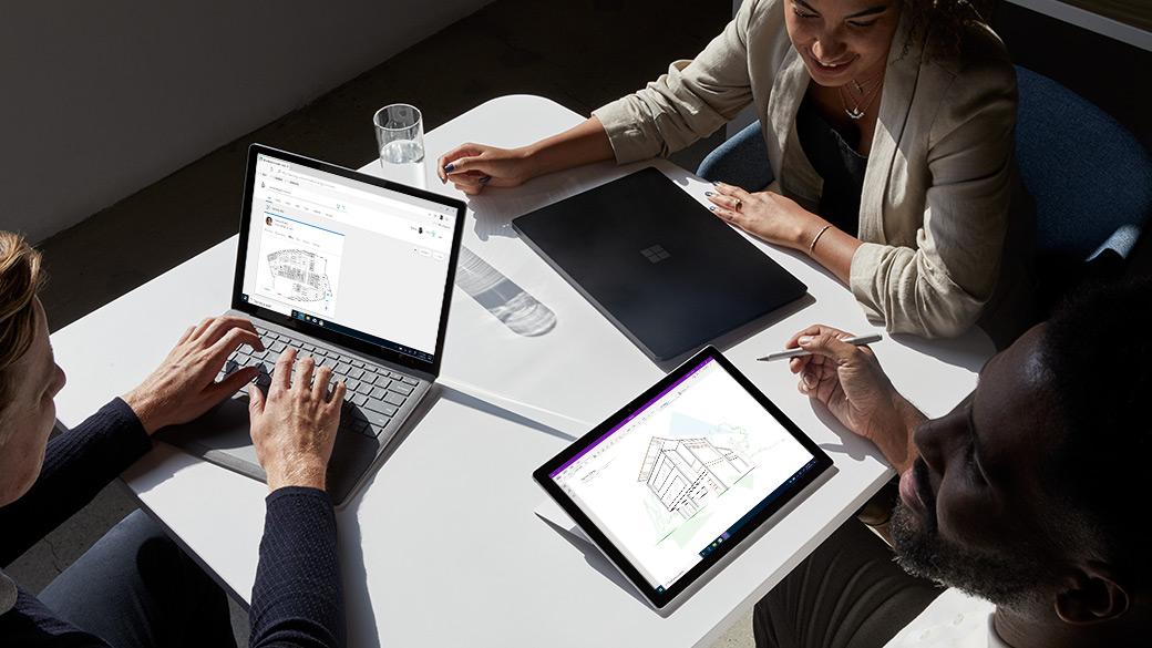 Drei Mitarbeiter, die mit ihren Surface Pro-Geräten zusammenarbeiten