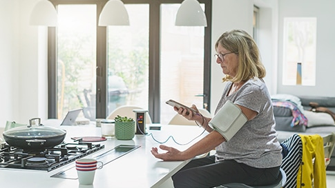 A woman in a kitchen using a smartphone.