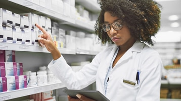 Female healthcare professional in a pharmacy setting pointing to a medication on a shelf and cross-referencing information on the tablet she is holding