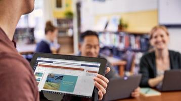 Ein Mann hält ein Tablet in der Hand, auf dem Microsoft Teams zu sehen ist. Er steht vor einem Mann und einer Frau mit Laptop vor sich.