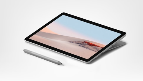 Surface Go 2 for Business och penna och med skärmen liggande platt i studioläge