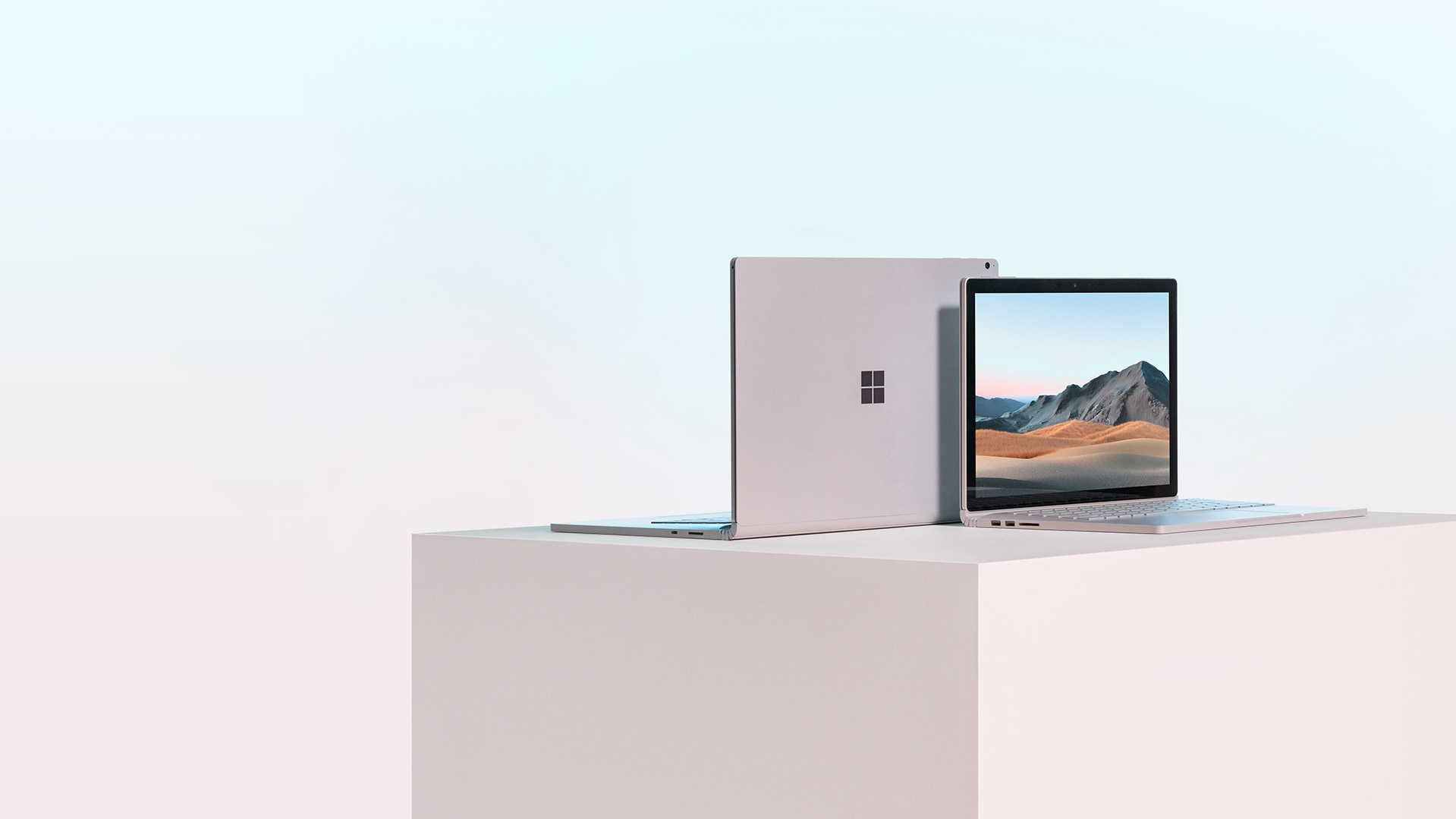 Front and rear view of two Surface Book 3 for Business devices with lids open on tabletop, one showing screen