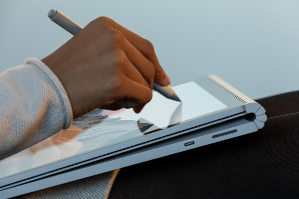 Person at desk holding Surface Book 3 for Business screen above keyboard