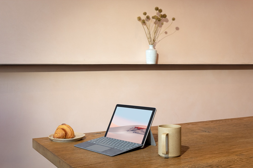 Een persoon zit aan tafel met Surface Go 2 voor zakelijk gebruik-tablet