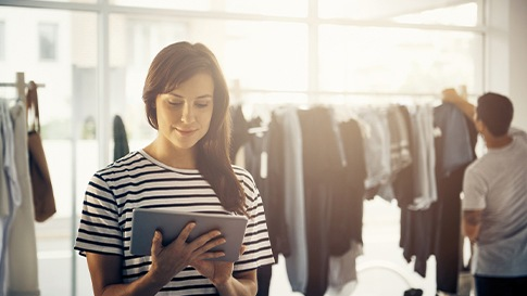 woman with a tablet in a clothing store