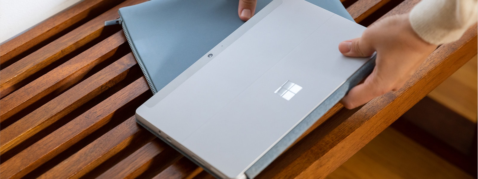 A woman picks up Ice Blue Sochi with a Surface Go 2