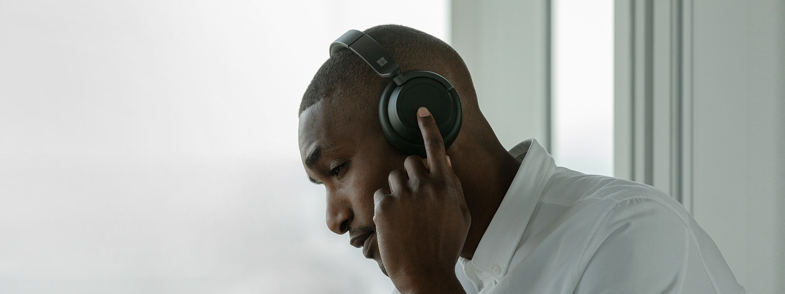 A man wears the black Headphones 2 while touching the left dial