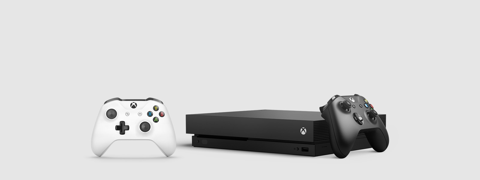 Xbox One X console with black and white Xbox One controllers.