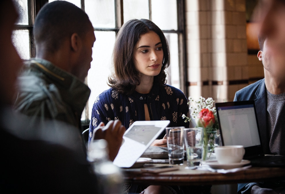 Three people seated at a table in a coffee shop. One person is using a tablet and pen, and another person is using a laptop.