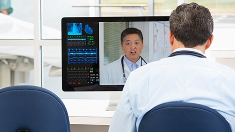 A doctor in a hospital having a video conference with another doctor to discuss a patient