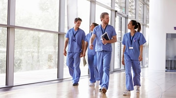 Four healthcare workers in scrubs walking in a healthcare facility. One of them is carrying a tablet