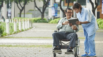 A man in a wheelchair and a woman standing next to him both looking at a tablet