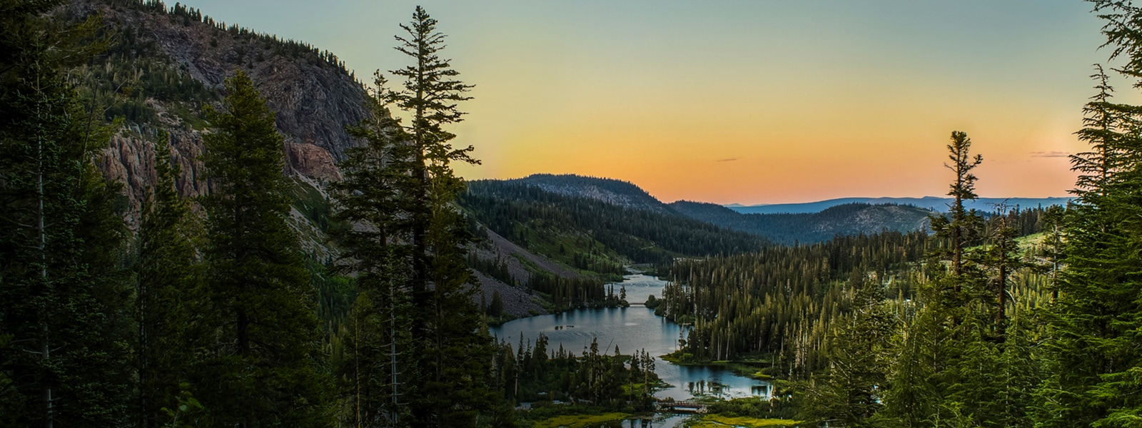 A lake reflects a sunrise in a forested mountain valley