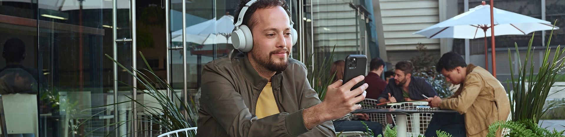 A person with headphones looking at a mobile device.