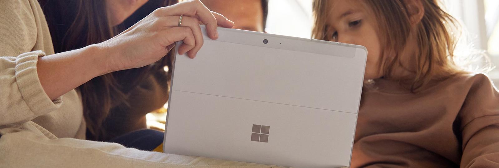 Um homem sentado em um banco fora de seu escritório enquanto olha para o Surface Go 2 no modo tablet