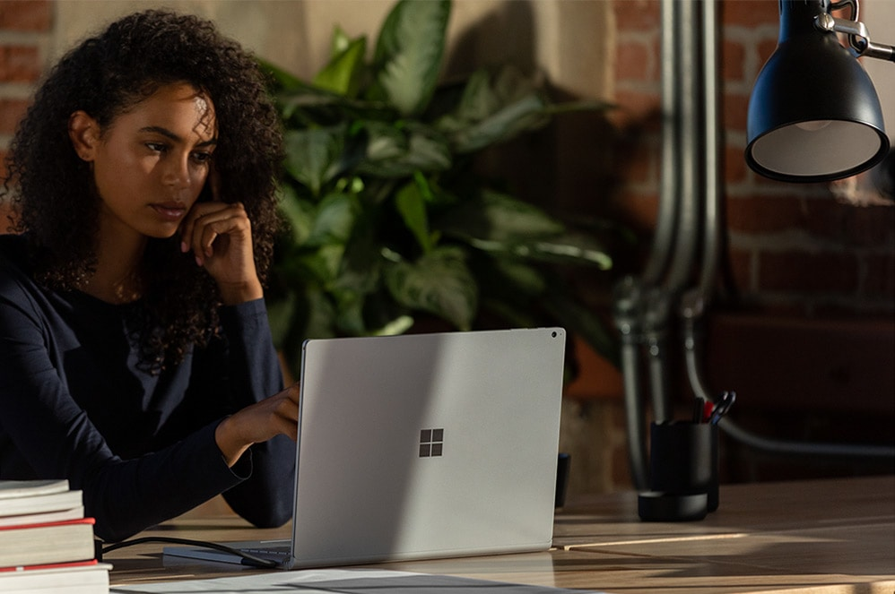 A woman works on Surface Book 3 in laptop mode