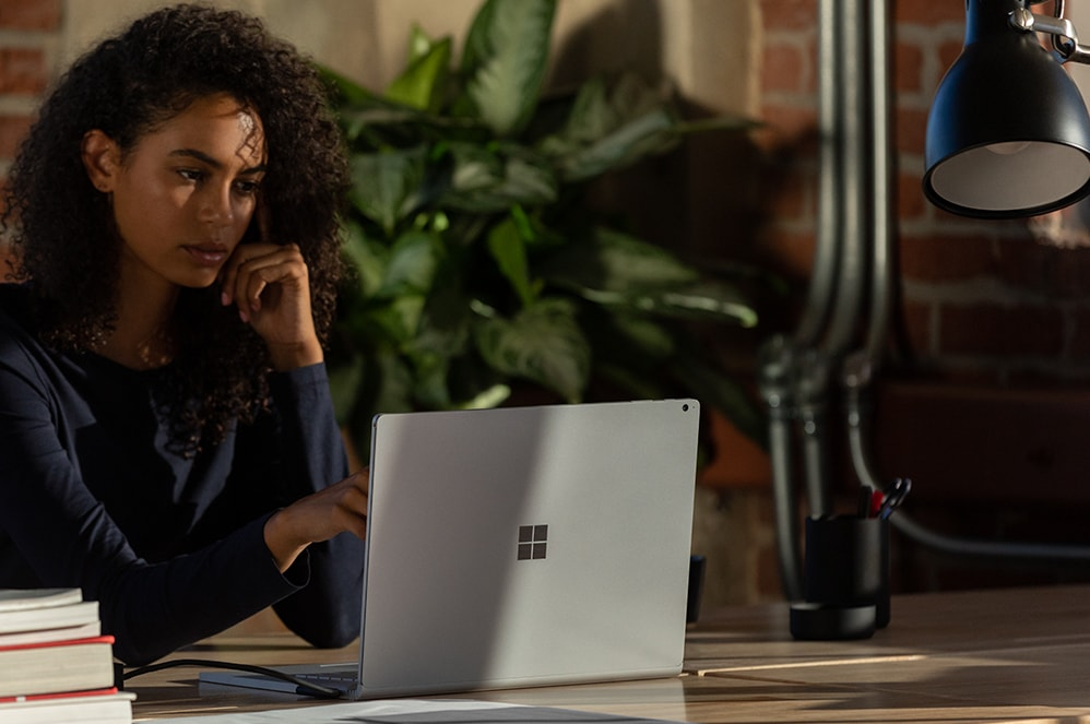 Person sitting at desk looking at Surface Book 3 for Business screen