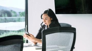 Uma pessoa sentada em uma mesa de conferência olhando para um telefone celular