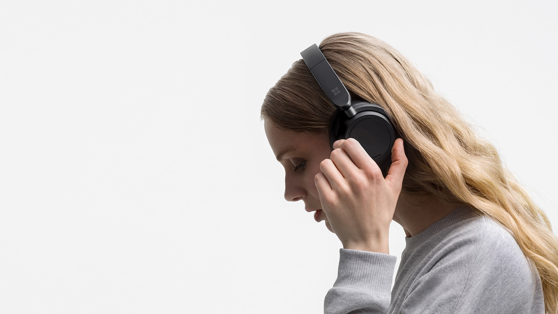 a woman turns the left dial on the left side of Surface Headphones 2