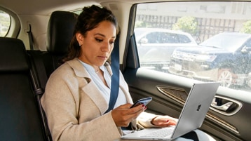 Uma pessoa sentada no banco de trás de um carro usando um laptop e olhando para um telefone celular
