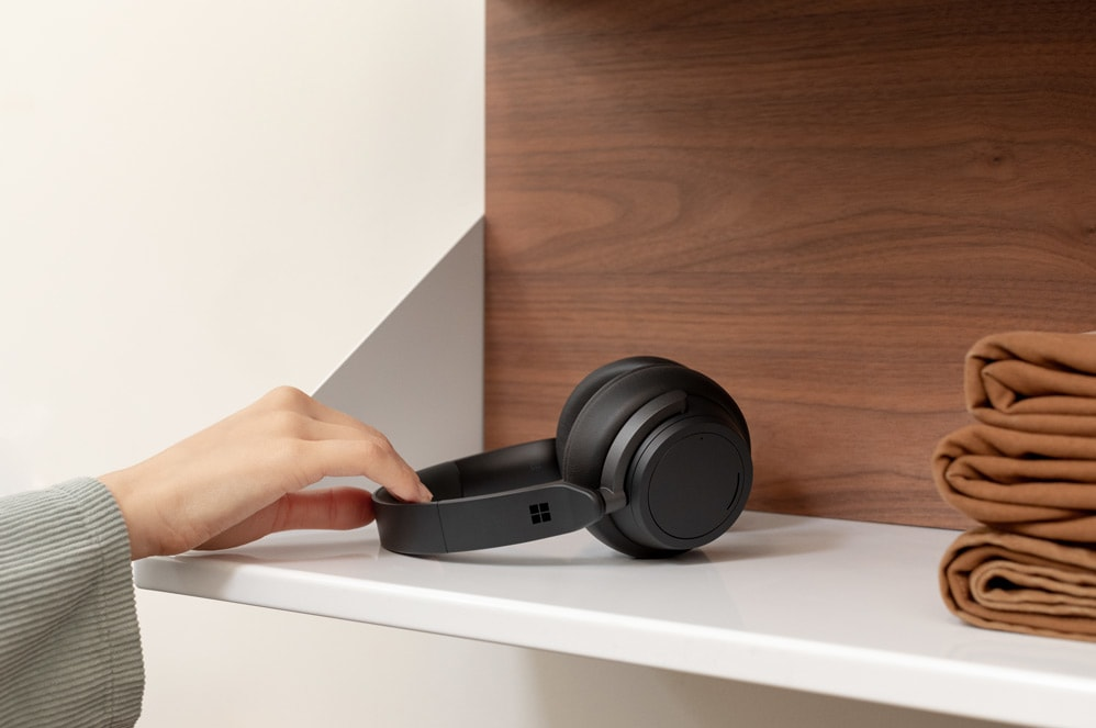 A person picks up Surface Headphones 2 off of a shelf