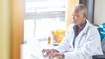 Doctor working in-front of a laptop