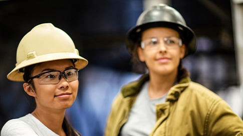 Two women at a factory with security helmets