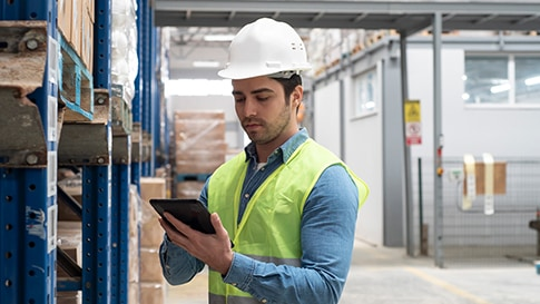 A worker in a storage warehouse, using a tablet.