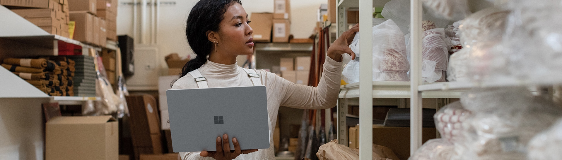 A person looking at items on a shelf in a stock room while holding an open Surface laptop