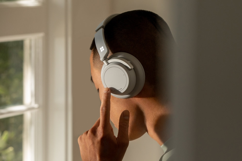 A man uses the left on-ear dial to adjust noise cancellation on Surface Headphones 2