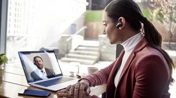 Eine Frau mit Headset im Ohr telefoniert an ihrem Laptop mit einem Mann, der auf dem Screen zu sehen ist.