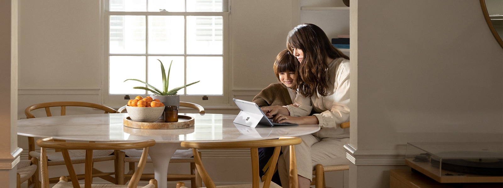 A woman sites at a dining table with her son playing on Surface Go 2
