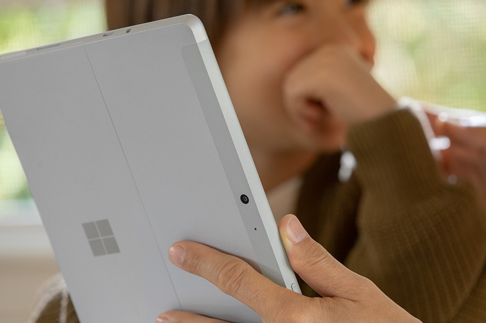 A woman holds Surface Go 2 while her young son looks on.