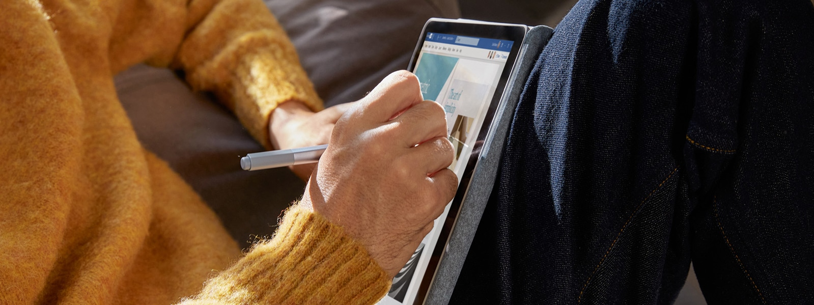 A woman uses Surface Pen to write on Surface Go 2 in studio mode