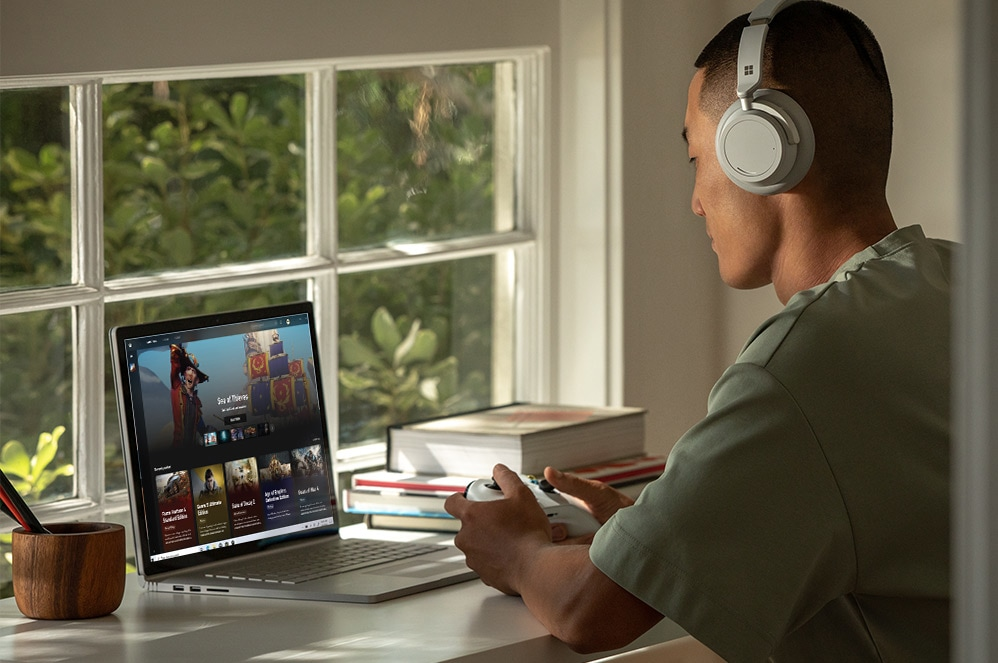 A man plays an Xbox game on Surface Book 3 with an Xbox controller while wearing Surface Headphones