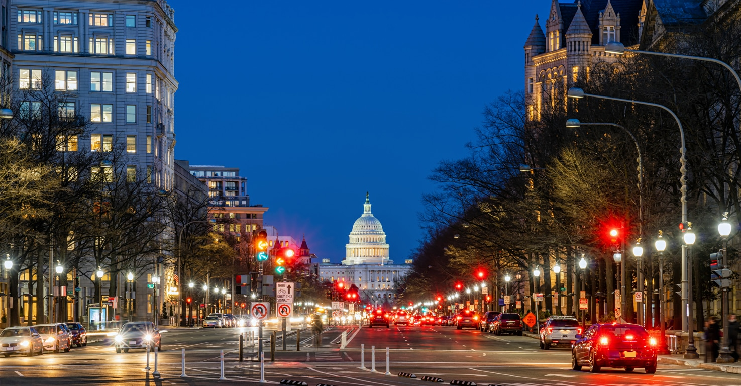 Traffic at night on a busy street in Washington, DC, with the United States Capitol building in the background.