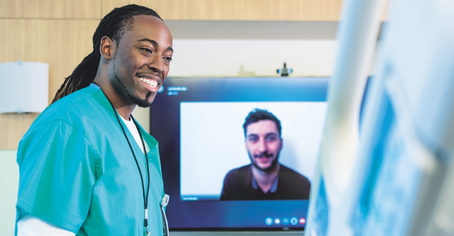 A healthcare professional in medical scrubs is standing in a patient's room while a person joins via a video conference call displayed on a wall-mounted monitor