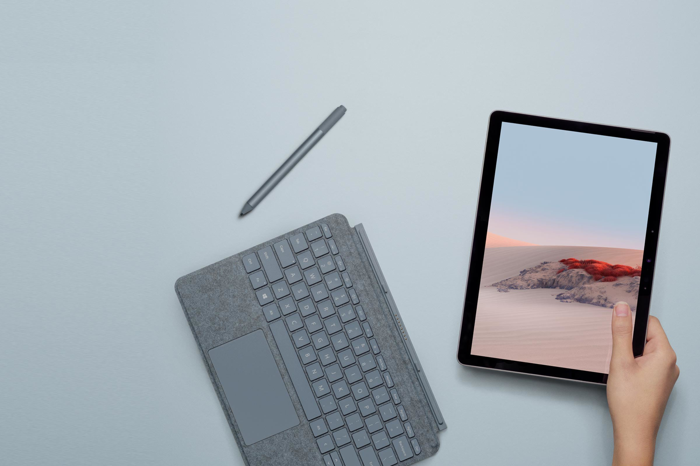 A woman's hand holds Surface Go 2 next to a Type Cover and Surface Pen
