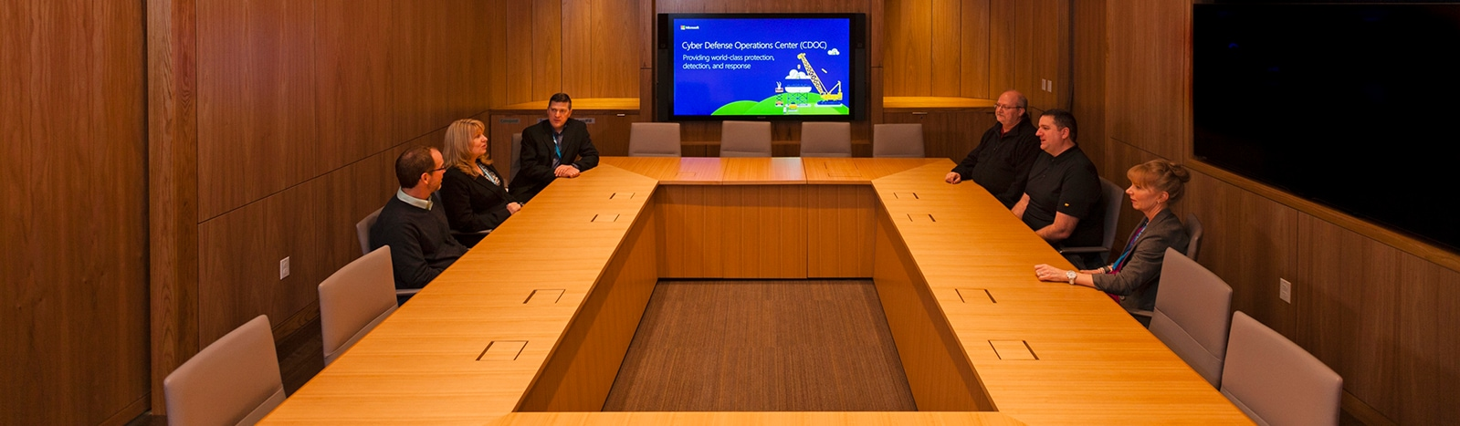 Six people seated in a large conference room talking while a large screen at the front of the room displays a presentation titled Cyberdefense Operations Center (CDOC)
