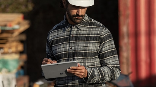 A worker in the field writes with Surface Pen on his Surface Go 2 in Tablet Mode