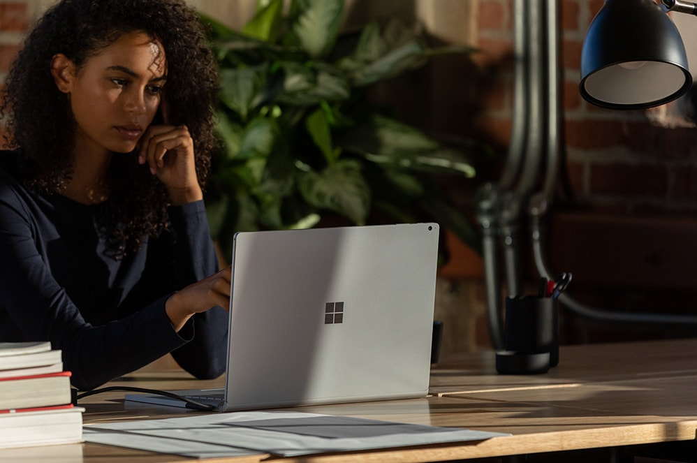 A woman working on a Surface Book 3 in an open office