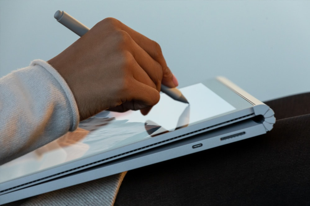 A person sketches with Surface Pen on their Surface Book 3 in studio mode