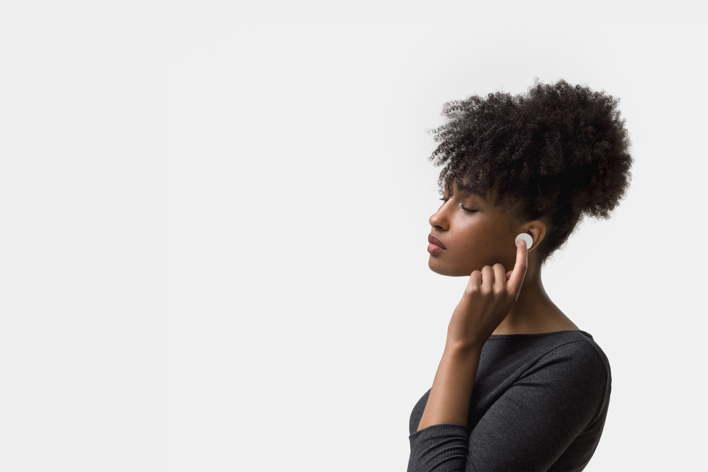 A woman touches Surface Earbuds in her left ear.