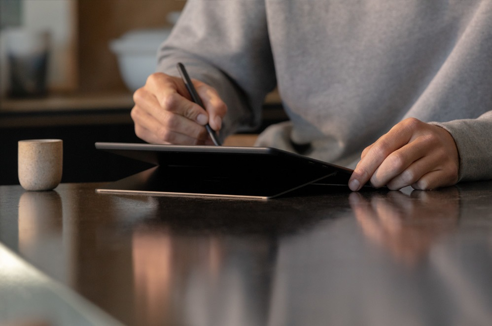 A person writes with Surface Pen on a Surface device in studio mode