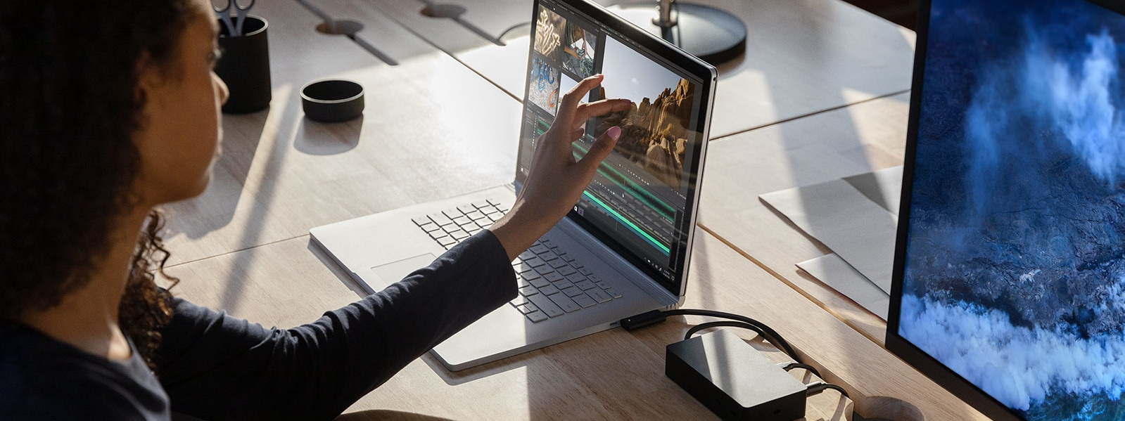 A woman interacts with Adobe Premier Pro on her Surface Book 3, which is connected to a 4K monitor on her desk