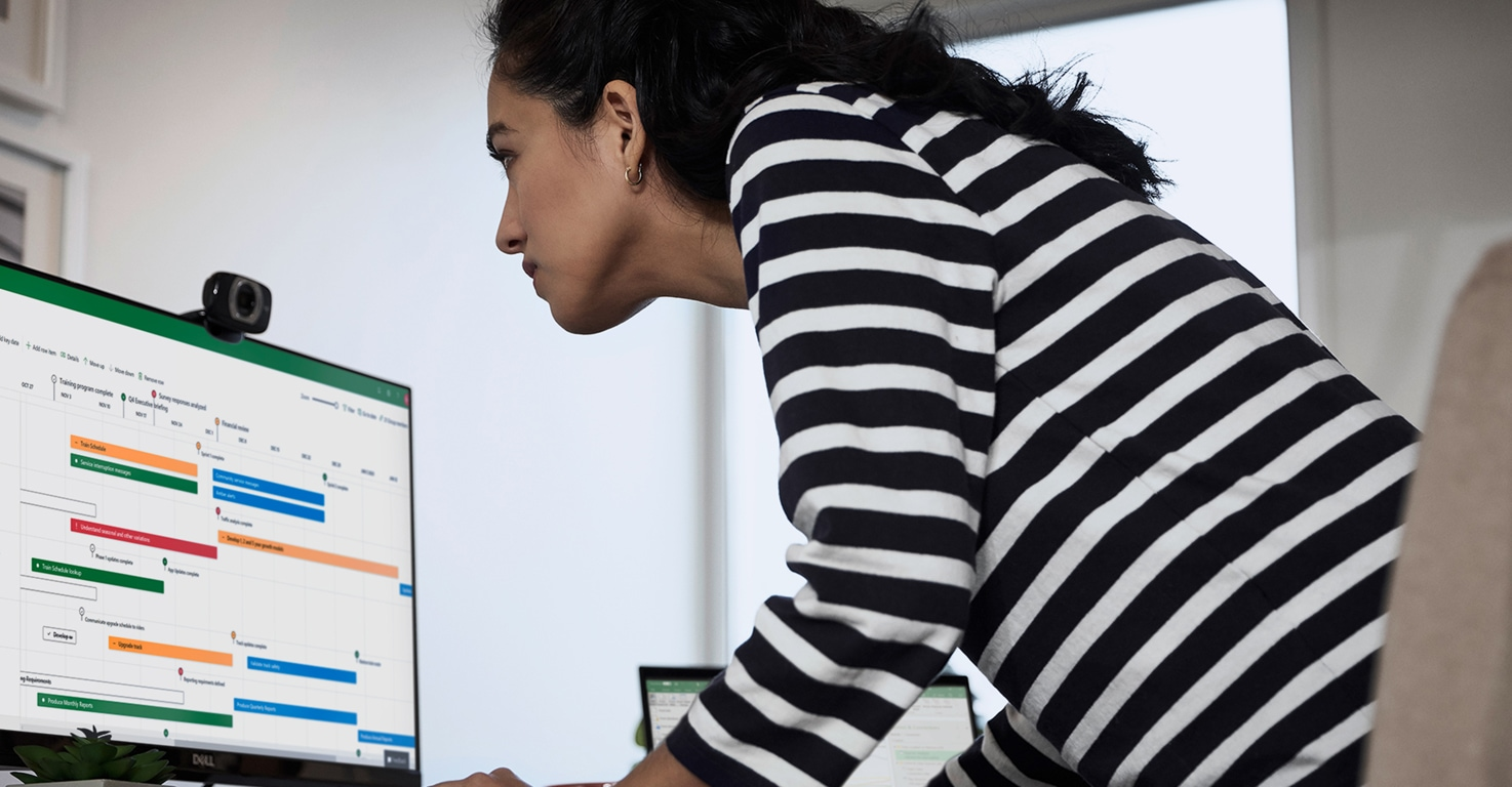 Person working at a desk looking at a Microsoft Project timeline open on the screen of a large desktop monitor.