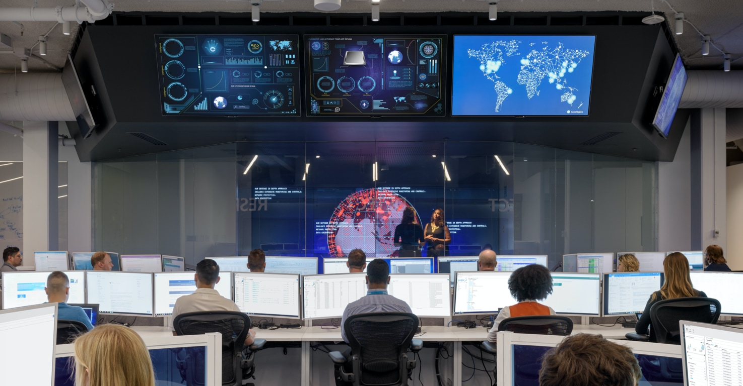 The Microsoft Cyberdefense Operations Center with security professionals working in front of arrays of display monitors.